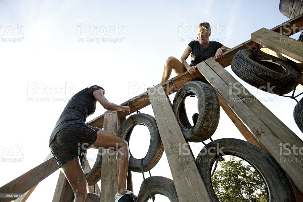 women climbing over the wall of tires stock photo