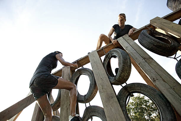 women climbing over the wall of tires women climbing over the wall of tires obstacle course stock pictures, royalty-free photos & images