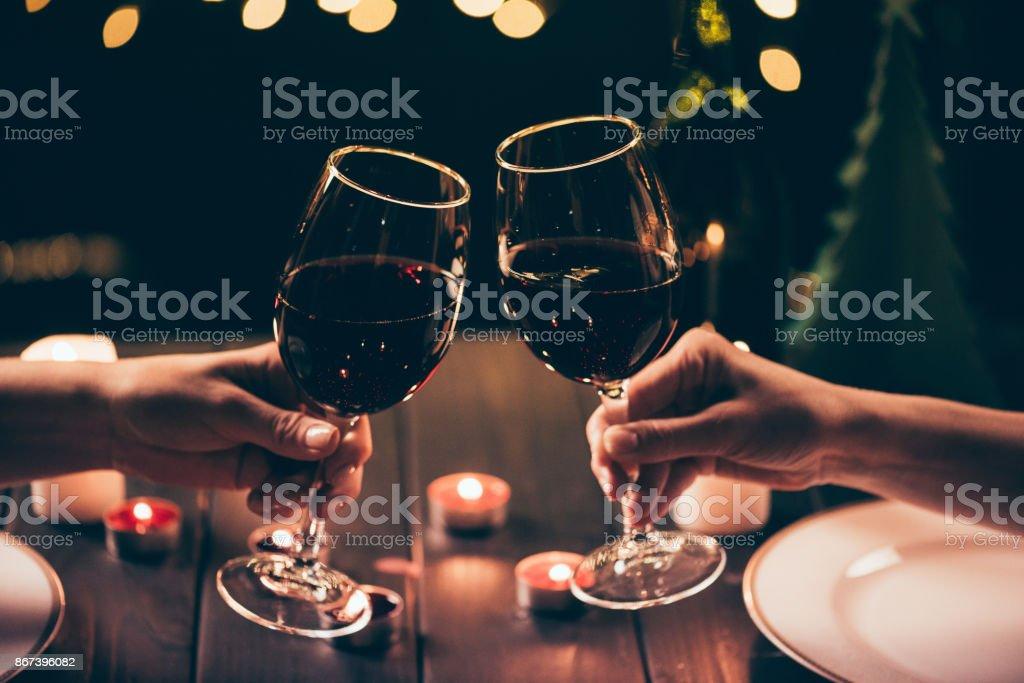 mujeres tintinear vasos sobre la mesa servida - foto de stock