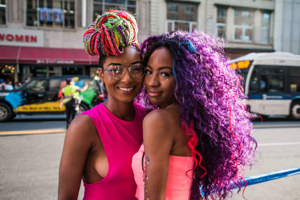 women couple smiling at nyc pride parade - transsexual stock photos and pictures