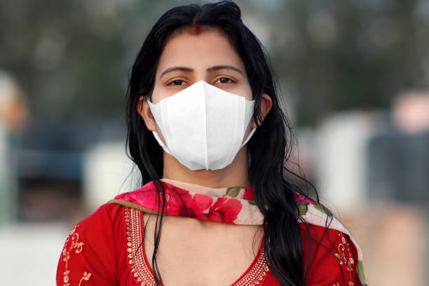 Women covering her face with pollution mask for protection from viruses like COVID-19 stock photo