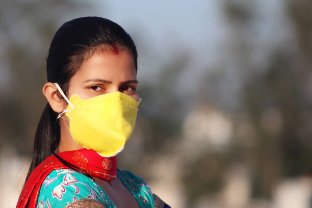 Women covering her face with pollution mask for protection from viruses stock photo