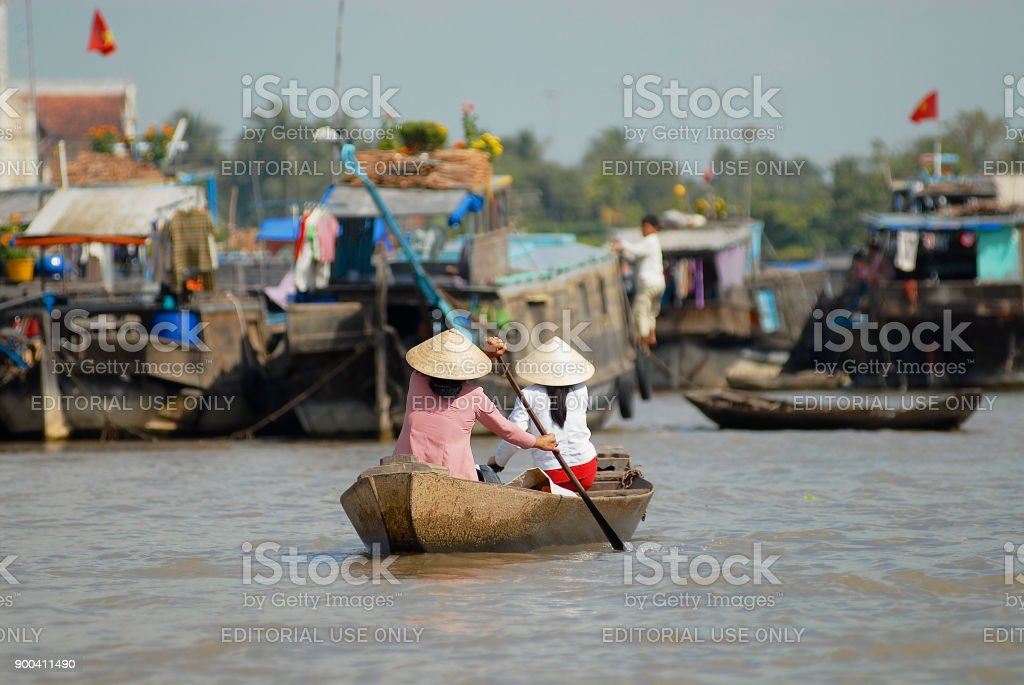 Women cross Mekong river by paddleboat at the famous floating market in Cai Be, Vietnam. stock photo