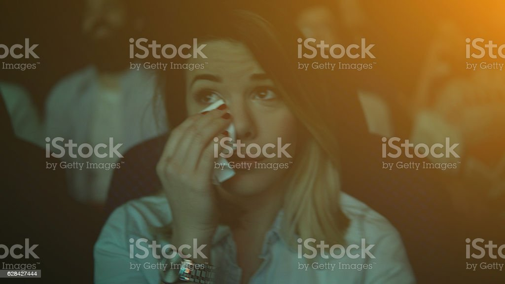Women crying while watching movie in a cinema hall stock photo