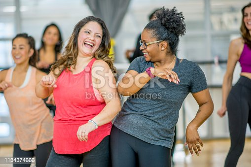 A multi-ethnic group of adult women are dancing in a fitness studio. They are wearing athletic clothes. Two women are laughing while dancing together.