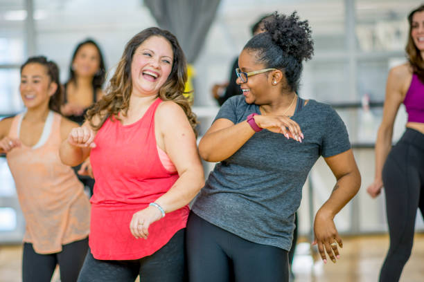 Women Dancing Together A multi-ethnic group of adult women are dancing in a fitness studio. They are wearing athletic clothes. Two women are laughing while dancing together. exercising stock pictures, royalty-free photos & images