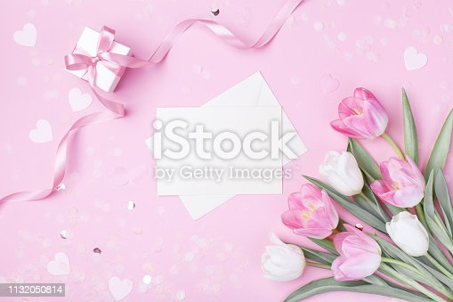 659293084 istock photo Women Day, Mother day background with envelope, gift box and beautiful spring tulip flowers on pastel pink desk. Flat lay. 1132050814