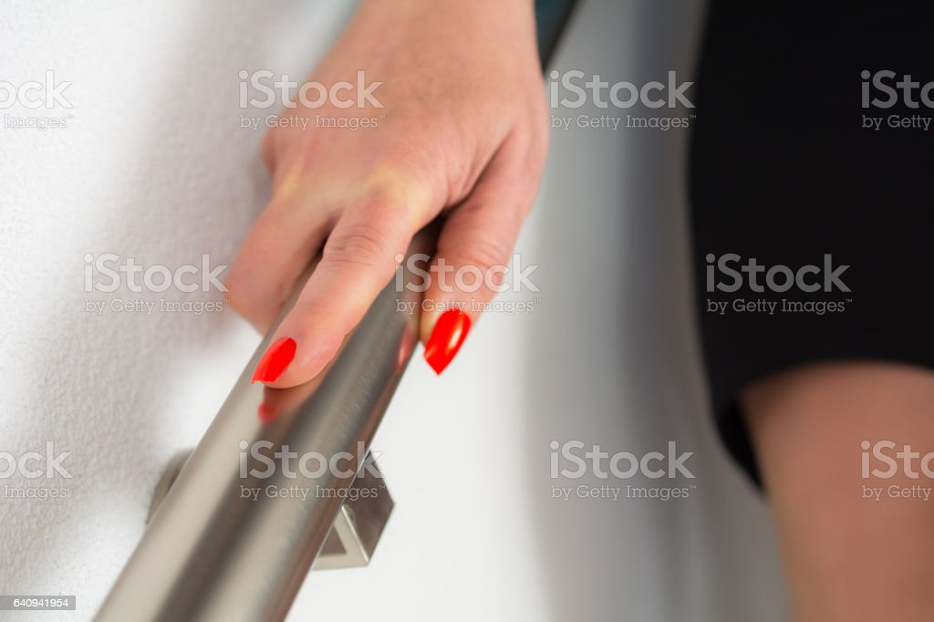 Women decending stairs with focus on her hand stock photo