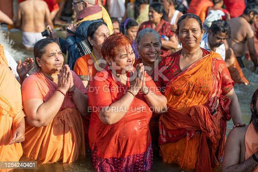 Indian women devotees, wearing red and orange, clasping hands and praying. They are taking the holy dip, surrounded by a crowd, in the Royal bath day. Photo taken during Kumbh Mela 2019 in Prayagraj (Allahabad), India.  Kumbh Mela or Kumbha Mela is a major pilgrimage and festival in Hinduism, and probably the greatest religious festival in the World. It is celebrated in a cycle of approximately 12 years at four river-bank pilgrimage sites: the Allahabad (Ganges-Yamuna Sarasvati rivers confluence), Haridwar (Ganges), Nashik (Godavari), and Ujjain (Shipra). The festival is marked by a ritual dip in the waters, but it is also a celebration of community commerce with numerous fairs, education, religious discourses by saints, mass feedings of monks or the poor, and entertainment spectacles. Pilgrims believe that bathing in these rivers is a means to cleanse them of their sins and favour a better next incarnation.