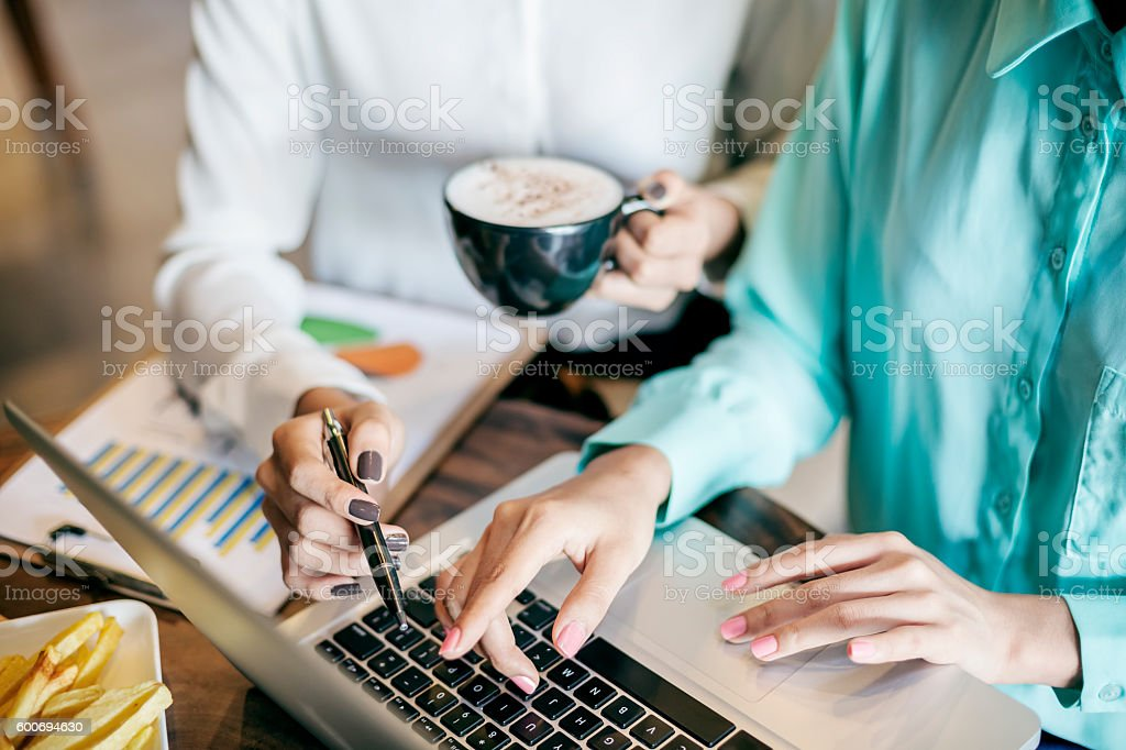 women discussing work at a coffee shop stock photo