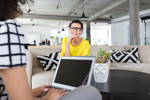 Women Discussing Work In Creative Workplace Stock Photo - Download Image Now