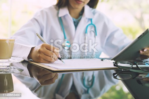 istock Women Doctors and patient are discussing something ,Having Consultation,Medical Pretty Doctor working in hospital writing a prescription, Healthcare and medically concept,selective focus 1148853497
