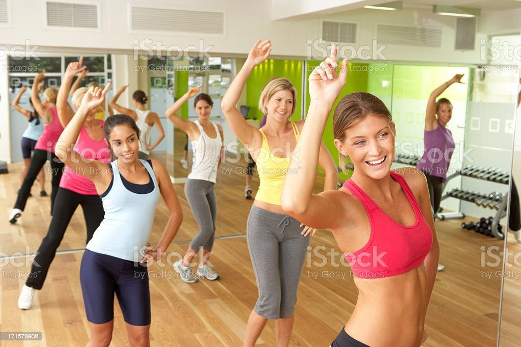 Women Doing A Fitness Class In Gym Women Taking Part In Fitness Class In Gym Smiling 20-29 Years Stock Photo