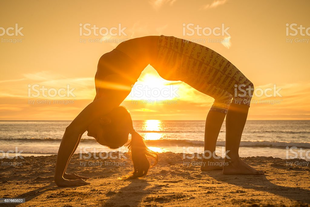 Women Doing Back Bend Yoga Pose By The Sea stock photo