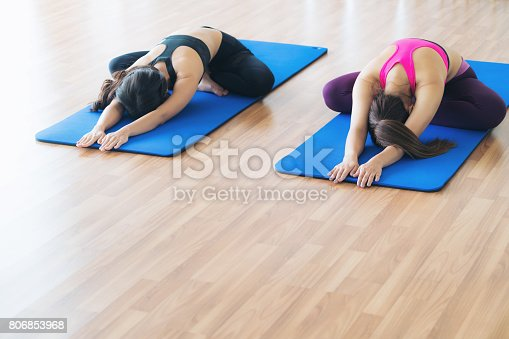 istock Women doing back stretching yoga in fitness gym 806853968