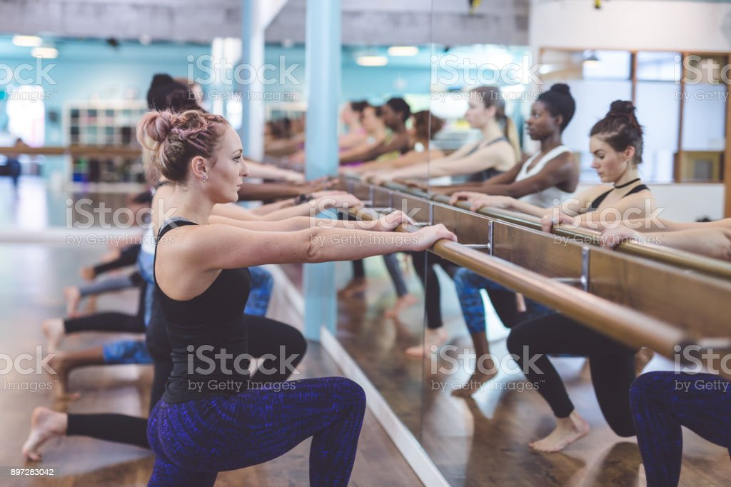 Women Doing Barre Workout Together at Modern Gym stock photo