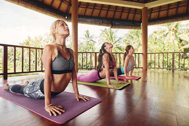Women doing cobra pose at yoga class Shot of young women doing cobra pose on exercise mat at yoga class. Three female doing core stretch on fitness mat. cobra pose stock pictures, royalty-free photos & images