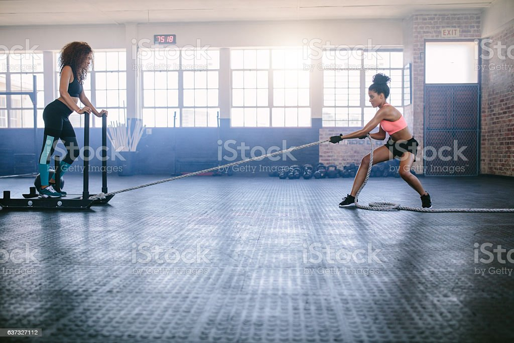 Women doing intense physical workout at gym stock photo