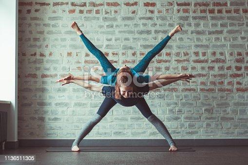 istock women doing partner yoga in yoga studio opposite brick wall 1136511305