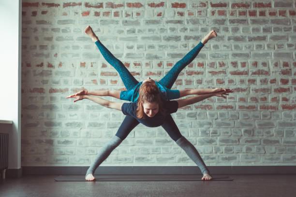 femmes faisant partenaire yoga dans le studio de yoga face mur de briques - Photo