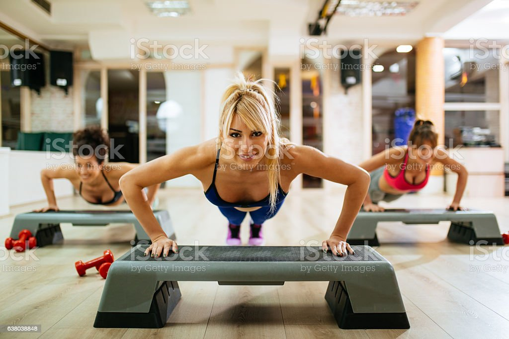 Women doing push-ups on step aerobics equipment at gym. - foto de acervo