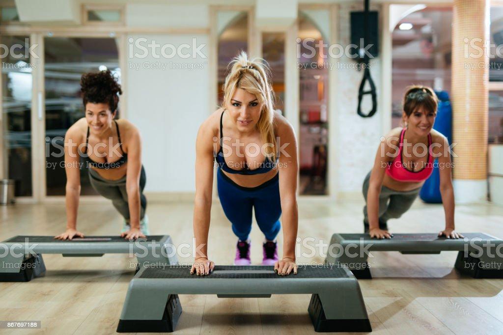 Mulheres fazendo flexões na etapa equipamentos de aeróbica no ginásio. - foto de acervo