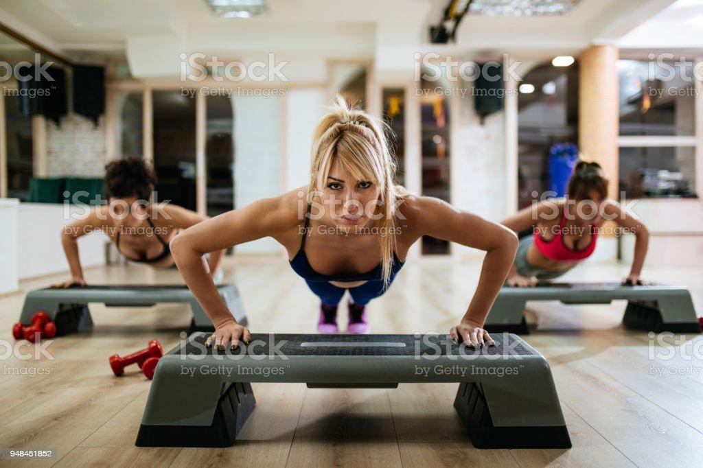 Mulheres fazendo flexões na etapa de equipamentos de aeróbica no ginásio - foto de acervo