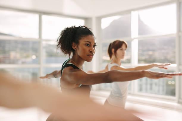 kobiety robią rozciąganie i trening jogi na siłowni - selektywna głębia ostrości zdjęcia i obrazy z banku zdjęć