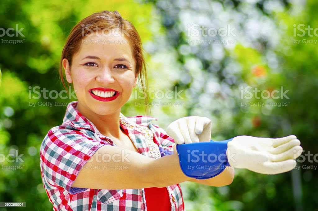 women dressed with colorfull clothes putting on work gloves Стоковые фото Стоковая фотография