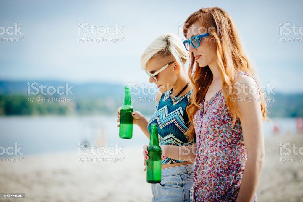 夏天在海灘上喝啤酒的婦女 免版稅 stock photo