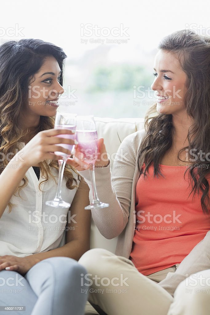 Women drinking champagne and clinking glasses stock photo
