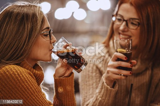 Close-up shot of two women having a refreshing drink at the bar.