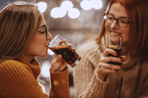 frauen trinken koks - alkoholfreies getränk stock-fotos und bilder