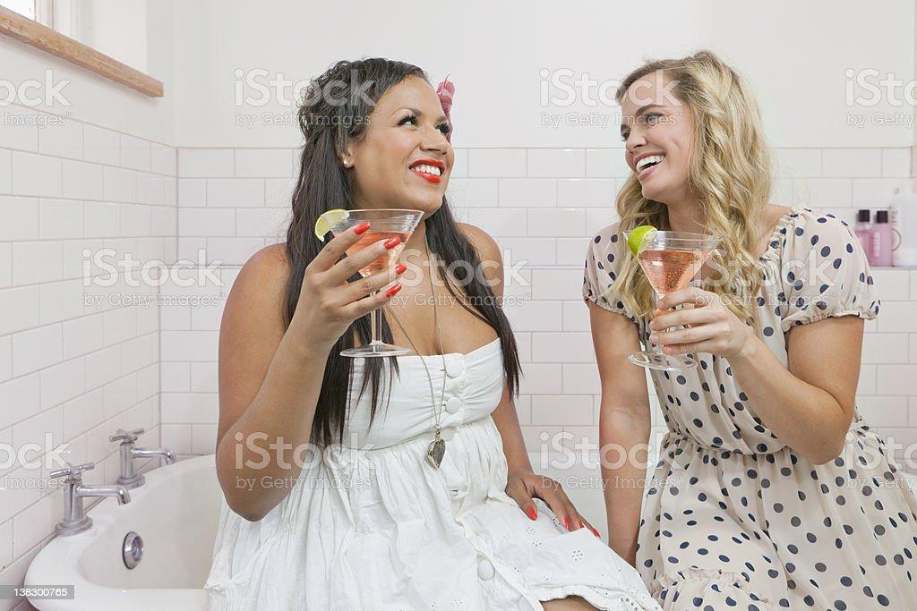 Women drinking martinis in bathroom stock photo