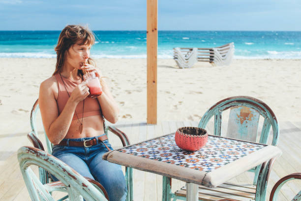 Women drinking smoothie on the beach stock photo