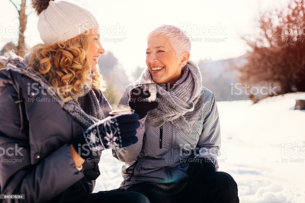 Women Drinking Tea Outdoors At Winter stock photo