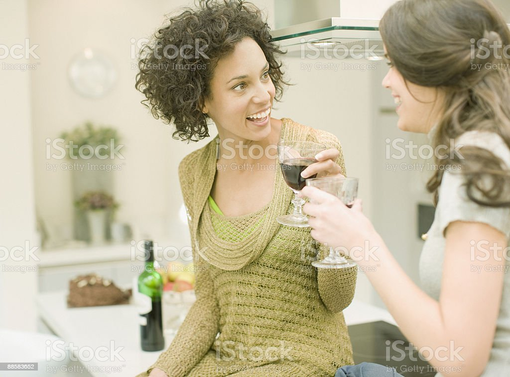 Women drinking wine in kitchen royalty-free stock photo