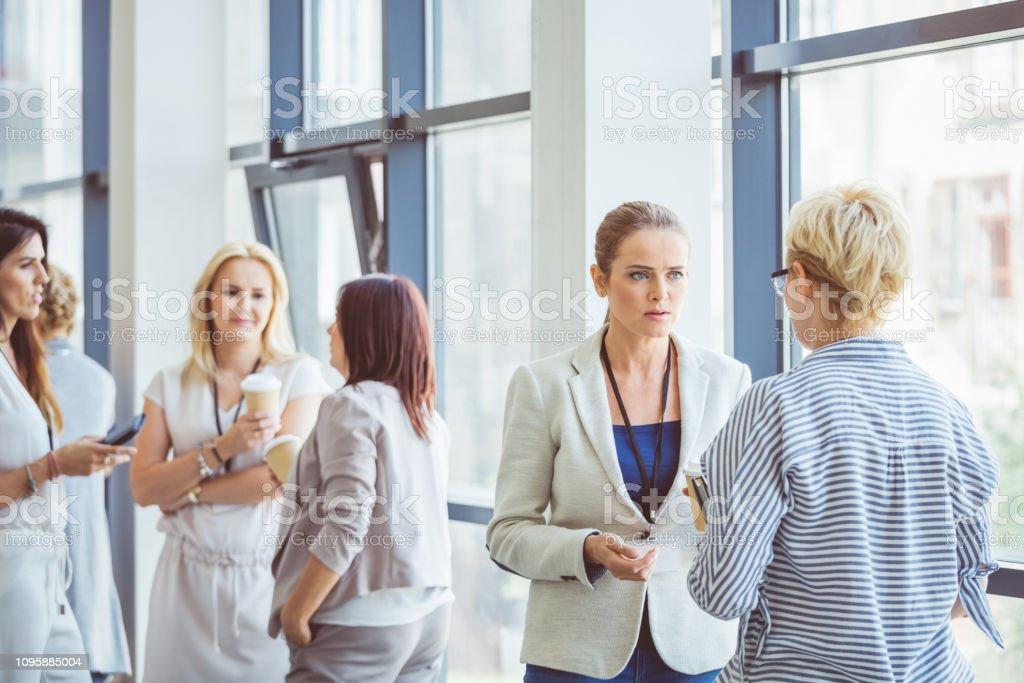 Women during a break in seminar Group of business women talking in office lobby during break. Women during a break in seminar. Adult Stock Photo