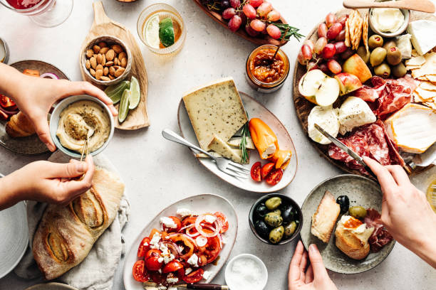 Women eating fresh Mediterranean platter on table High angle view of fresh meal on table. Women are eating healthy food. They are with Mediterranean platter. Eat more Calories stock pictures, royalty-free photos & images
