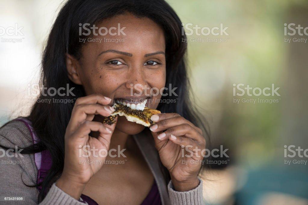 Women eating fresh pita with Za'atar. stock photo