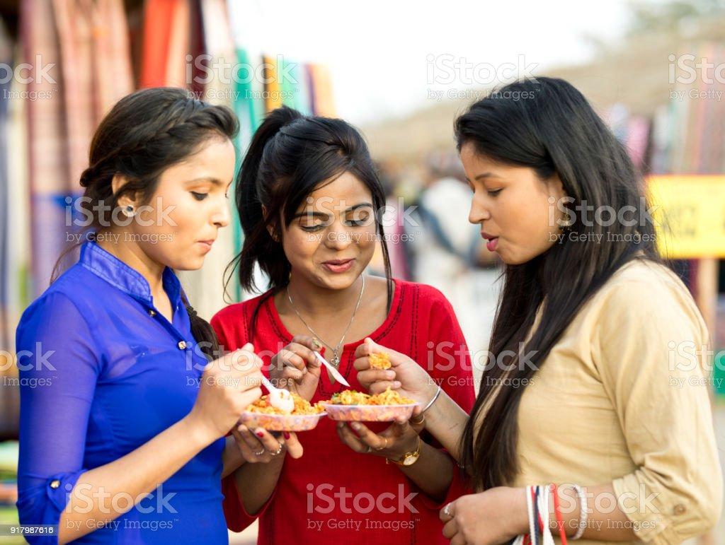Las mujeres comer snack en el mercado de la calle - foto de stock