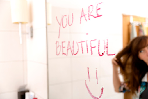 istock Women encouraging herself by writing words you are beautiful on mirror with lipstick 824316260