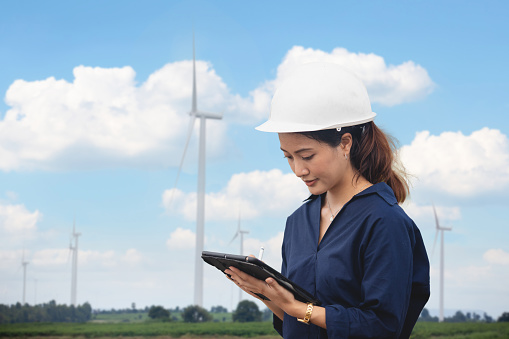 Women engineer using the tablet for working on-site at wind turbine farm