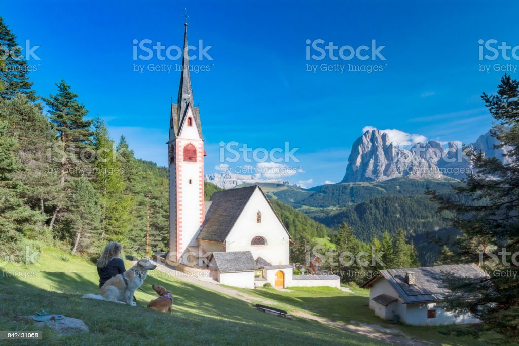 Women enjoy the view with her dogs, St Jacob church above Val Gardena in Dolomites stock photo