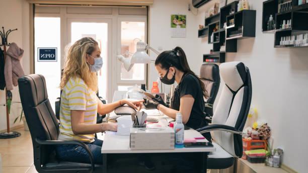 Frauen genießen Maniküre im Schönheitssalon während COVID-19 – Foto