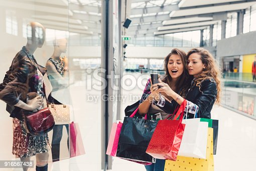Young women in the shopping mall taking selfie together