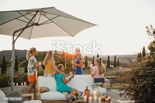 Small group of women are watching the sunset from the garden of their villa on holiday.