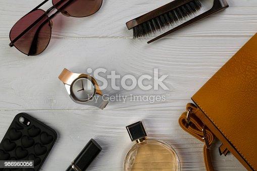 539853444 istock photo Women essentials fashion accessories on white wooden background 986960056
