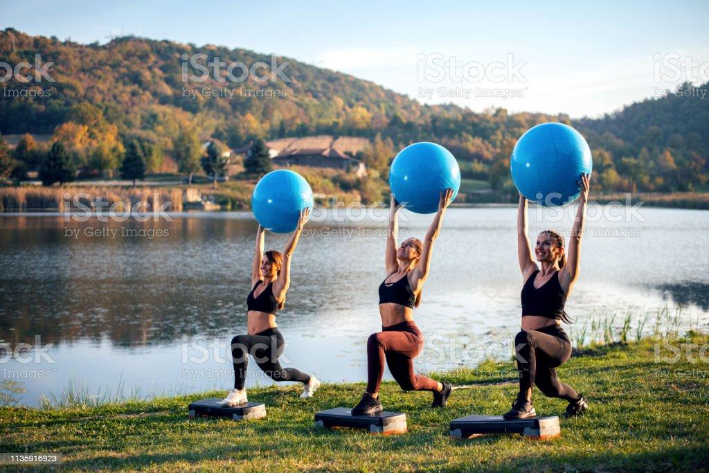 As mulheres exercitam ao lado do lago com esfera. - foto de acervo