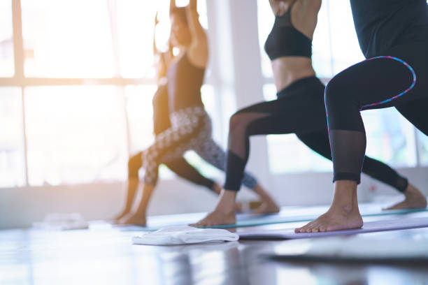 Women exercising in fitness studio yoga classes Women exercising in fitness studio yoga classes yoga class stock pictures, royalty-free photos & images